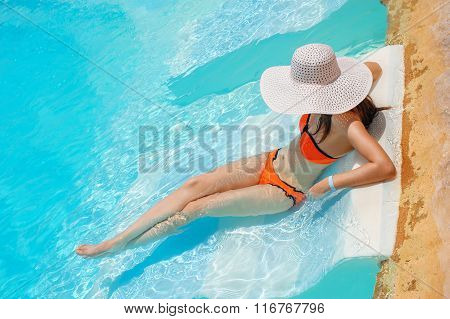 Young beautiful woman enjoying the sun and sitting on edge of the pool