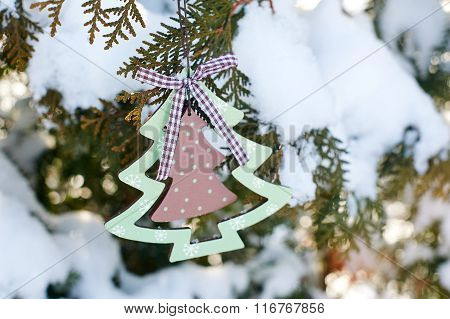 Beautiful wooden toys hanging on the Christmas tree in winter