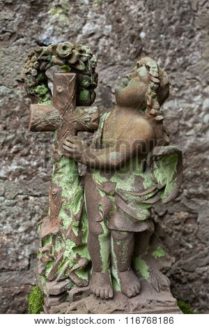 Angel with a cross covered with moss.