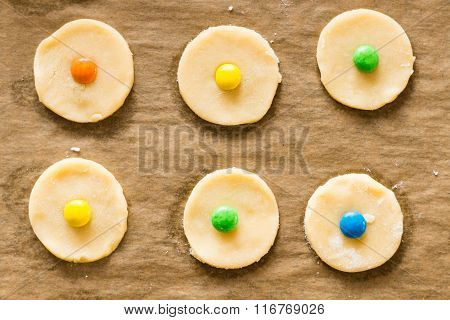 Baking cookies concept - fresh raw cookie dough on a baking tray with parchment paper