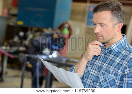 man reading in a welder workshop