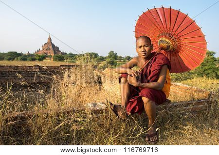 BAGAN, MYANMAR - DEC 13, 2015: Novice monk with red umbrella rests in front of Sulamani Pagodas. Bagan on December 13, 2015 in Bagan, Myanmar.