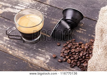 Coffee cup and capsules on a rustic wooden table
