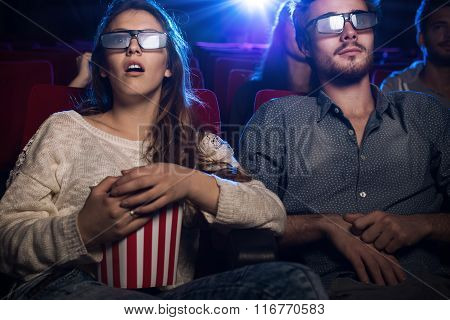 Young teenagers at the cinema wearing glasses and watching a 3d movie a girl is eating popcorn entertainment and movies concept
