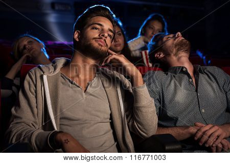Young People Watching A Boring Film At The Cinema