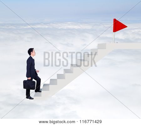 Business Man Stepping Up On Stairs To Red Flag With Cloud And Sky Background