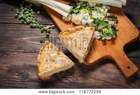 French Quiche Lorraine with ingredients on wood board