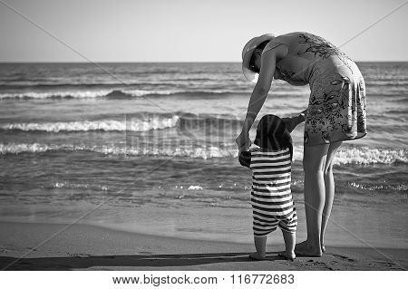 Mom Teaches A Child To Walk On The Beach