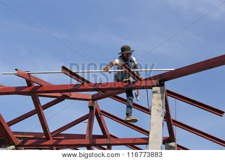 Worker Installing Structure Of Roof Steel For New House At Construction Site