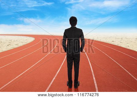 Businessman Standing On Running Track And Looking To Goal