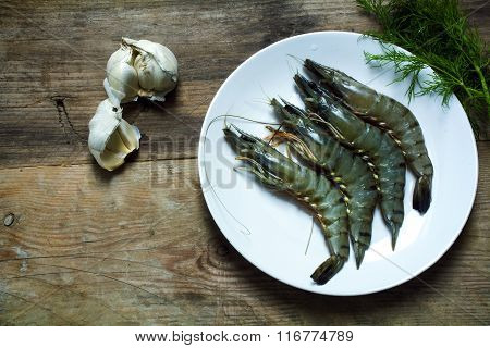 Raw Black Tiger Prawns On A Plate On A Rustic Wooden Board, Garlic And Dill Garnish, View From Above