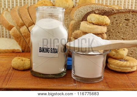 baking soda in a glass jar and wooden spoon with cookie and bread