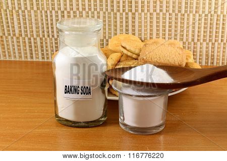 baking soda in a glass jar and wooden spoon with cookie