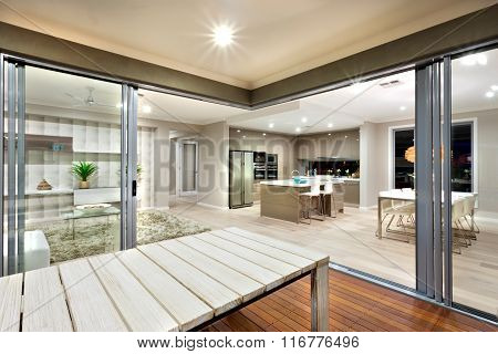 Inside View Of A Modern House Lights Turned On With Wooden Table  Sorrounded By Glass Doors.