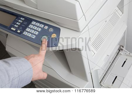 Side View Of Businessman Pressing Printer's Button In Office