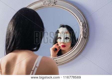 Portrait of beautiful mysterious young woman in carnival mask in front of the mirror