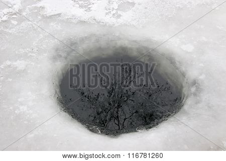 The Round Hole Carved Into The Ice. Winter Trees Reflected In Water