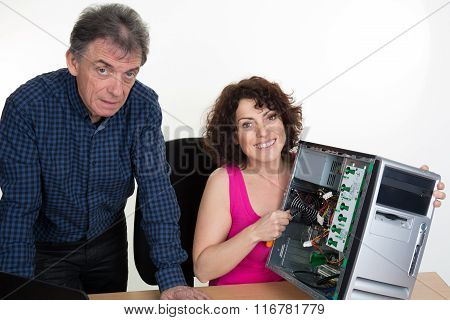 Woman Fixing A Computer At Office With Her Boss
