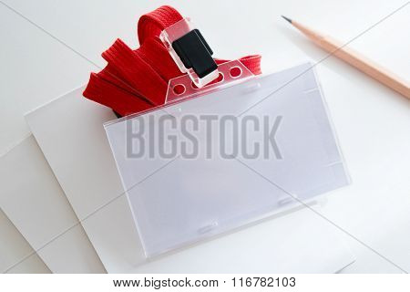 Blank ID or security card on office table, with red neck strap.