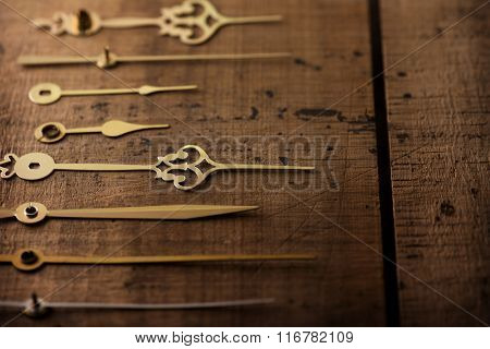 Clock hands or needle aligned on old wooden surface. Time concept image. Focus on center needle. Shallow depth of field.