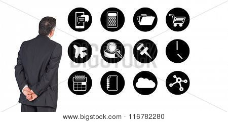 Mature businessman looking and considering against telephone apps icons