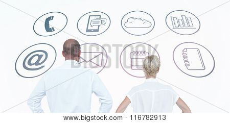 Smiling business people with hands on the hips against app icons Smiling business people back to the camera with hands on the hips