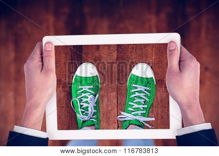 Feminine hands holding tablet against weathered oak floor boards background