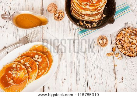 Pancakes with caramel and nuts on an old wooden background.