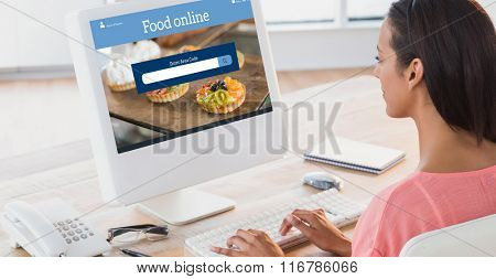 Businesswoman using computer at desk in creative office against food app