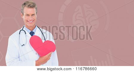 Smiling male doctor holding heart shape card against blue