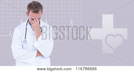 Male doctor suffering from headache against green background