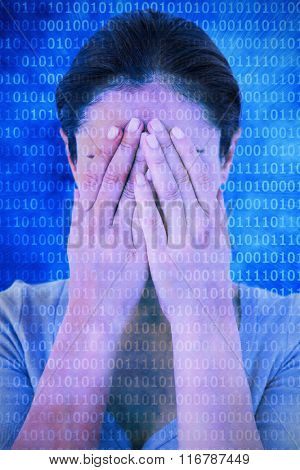 Sad woman hiding her face against glowing futuristic binary code