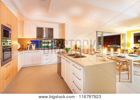 Kitchen And Dining Area Illuminated By Ceiling Lights And Flashing Candles