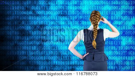 Redhead businesswoman scratching her head against shiny blue binary code on black background