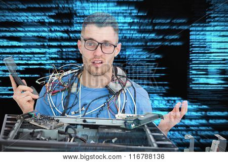 Confused it professional with cables and phone in front of open cpu against shiny blue coding on black background
