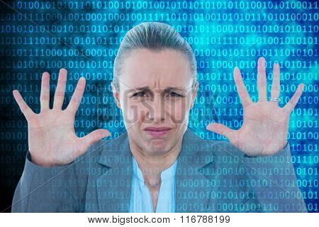 Upset businesswoman showing her hands against shiny blue binary code on black background