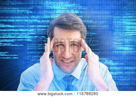 Young businessman with severe headache against shiny blue coding on black background