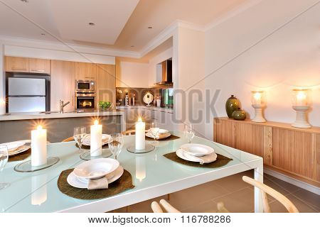 Closeup Of A Dining Table Setup In Front Of The Kitchen With Flashing White Candles