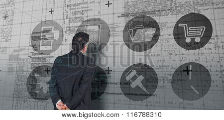 Mature businessman looking and considering against blue matrix and codes