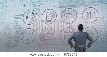 Businessman standing with hands on hips against blue matrix and codes