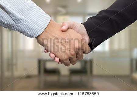 Close Up Of Businessmen Shaking Hands In Meeting Room