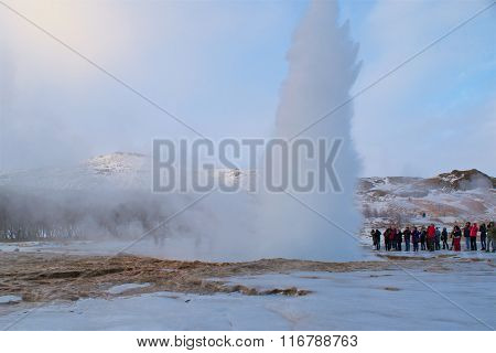 Haukadalur, Iceland - January 19, 2016:Tourists watching the eruption of Strokkur Geyser in Iceland