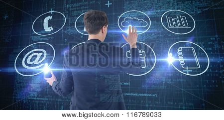 Wear view of businessman showing his hand against blue matrix and codes