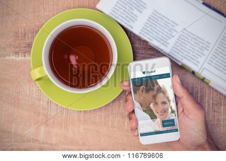 Dating website against cropped image of man holding smart phone