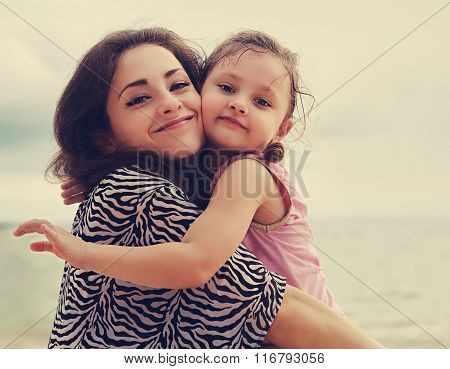 Happy Mother And Kid Girl Hugging With Natural Emotion Smiling On Blue Sea Background