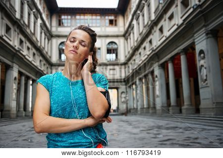 Portrait Of Relaxed Young Woman In Sportswear Listening Mp3