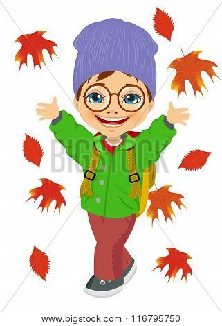 little boy wearing knitted hat playing with autumn leaves
