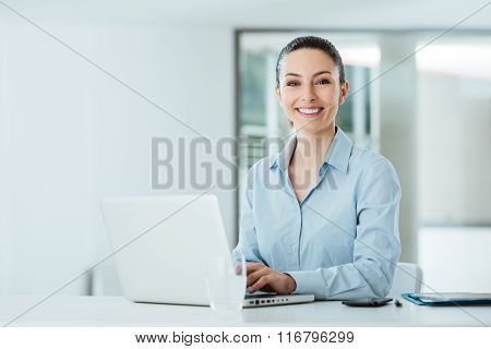 Smiling Young Businesswoman Working At Office Desk
