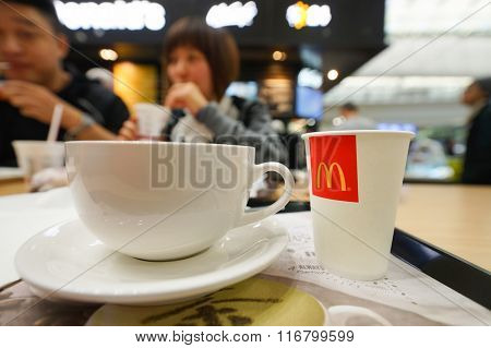 HONG KONG - JANUARY 29, 2016: close up shot of cup with flat white coffee on the table at McCafe. McCafe is a coffee-house-style food and drink chain, owned by McDonald's.