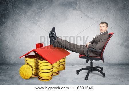 Businessman sitting on chair with coins and roof